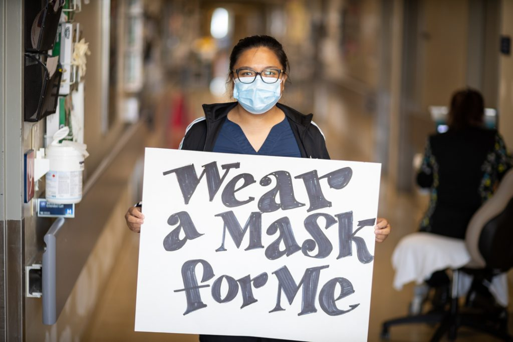 """A health care worker wearing a mask holds a large sign reading """"wear a mask for me"""""""