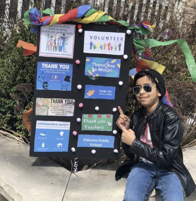 Daanish poses in front of a hand-made lawn sign, thanking healthcare workers during the pandemic