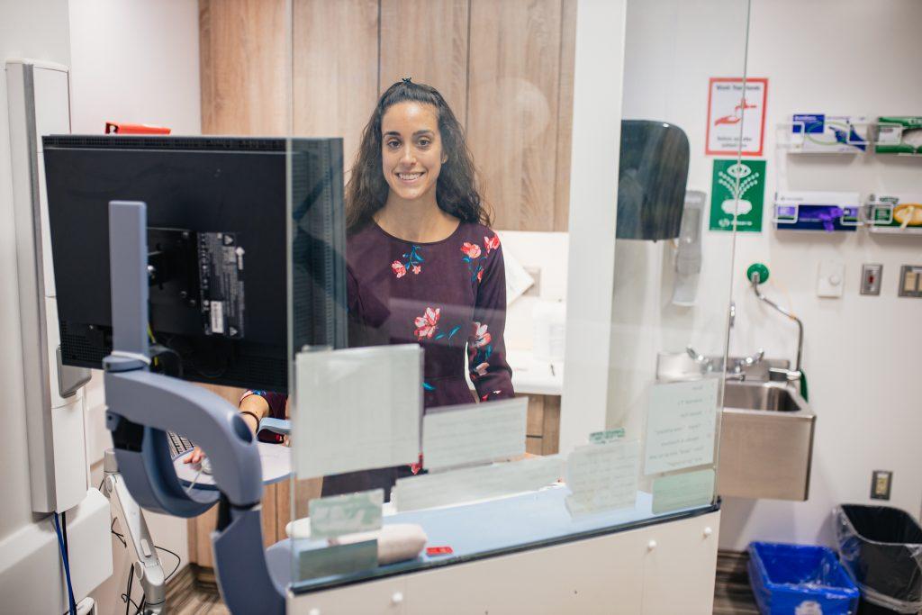 Lauren Harris stands at a desk behind a plexi-glass barrier
