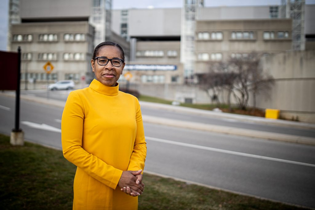 Leona Stewart standing in front of an HHS hospital site