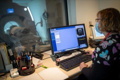 Photo of Jill Whiteley-Lamb sitting at a computer looking at an M R I image