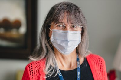 Lisa Petsche smiling at the camera wearing a medical grade face mask