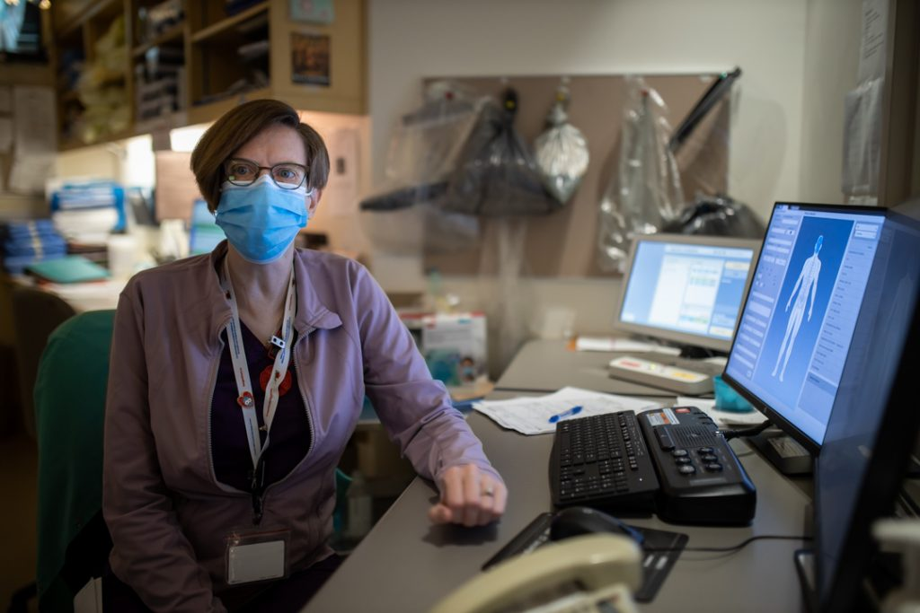 Colleen Hilbert sitting at her desk, wearing a medical face mask