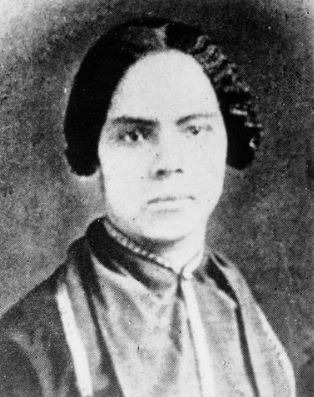 A black and white photo of a serious woman with her dress tied high at her neck.