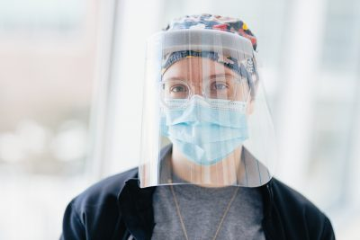A woman wears a hospital mask and face shield