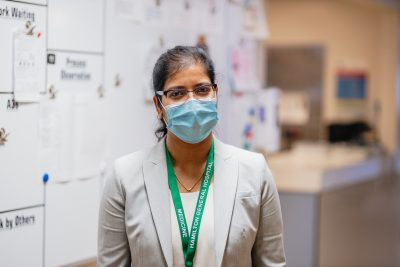 A woman wearing a hospital mask stands in front of a clinical whiteboard