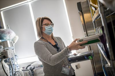 A woman wearing a hospital mask replaces supplies on a shelf