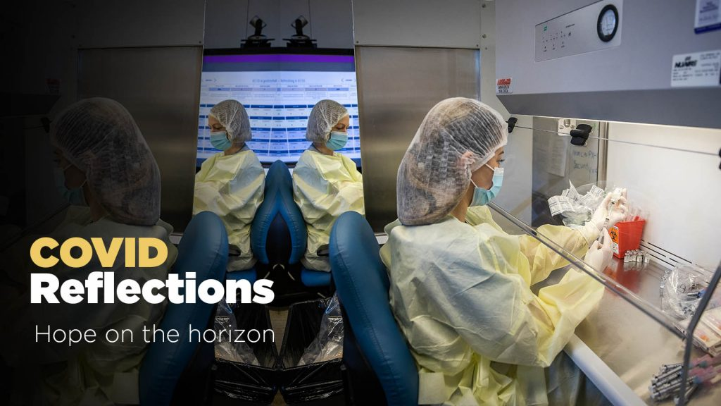 A lab worker holds a syringe behind a piece of glass. Text: COVID reflections: Hope on the horizon