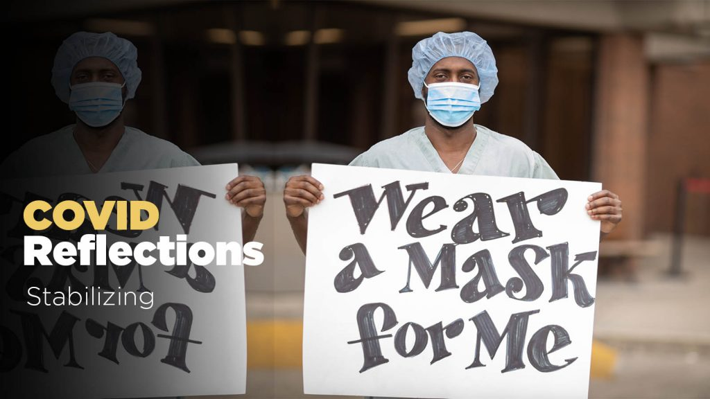 """A man wearing scrubs, a medical mask and a surgical cap holds a sign reading """"wear a mask for me."""" Text: COVID reflections - Stabilizing"""
