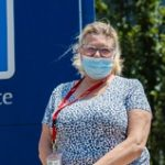 A woman wears a medical mask while standing outdoors near the Juravinski Hospital entrance sign