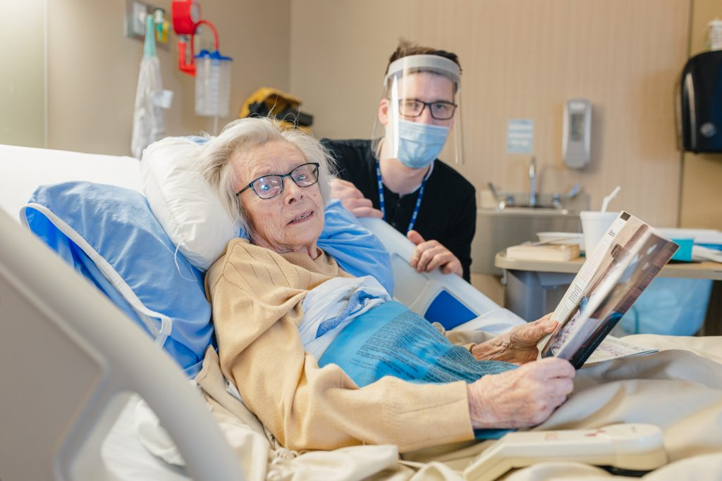 Malise Lynch smiles at the camera from her hospital bed. Elder life specialist Chris Gabor sits beside her wearing personal protective equipment.