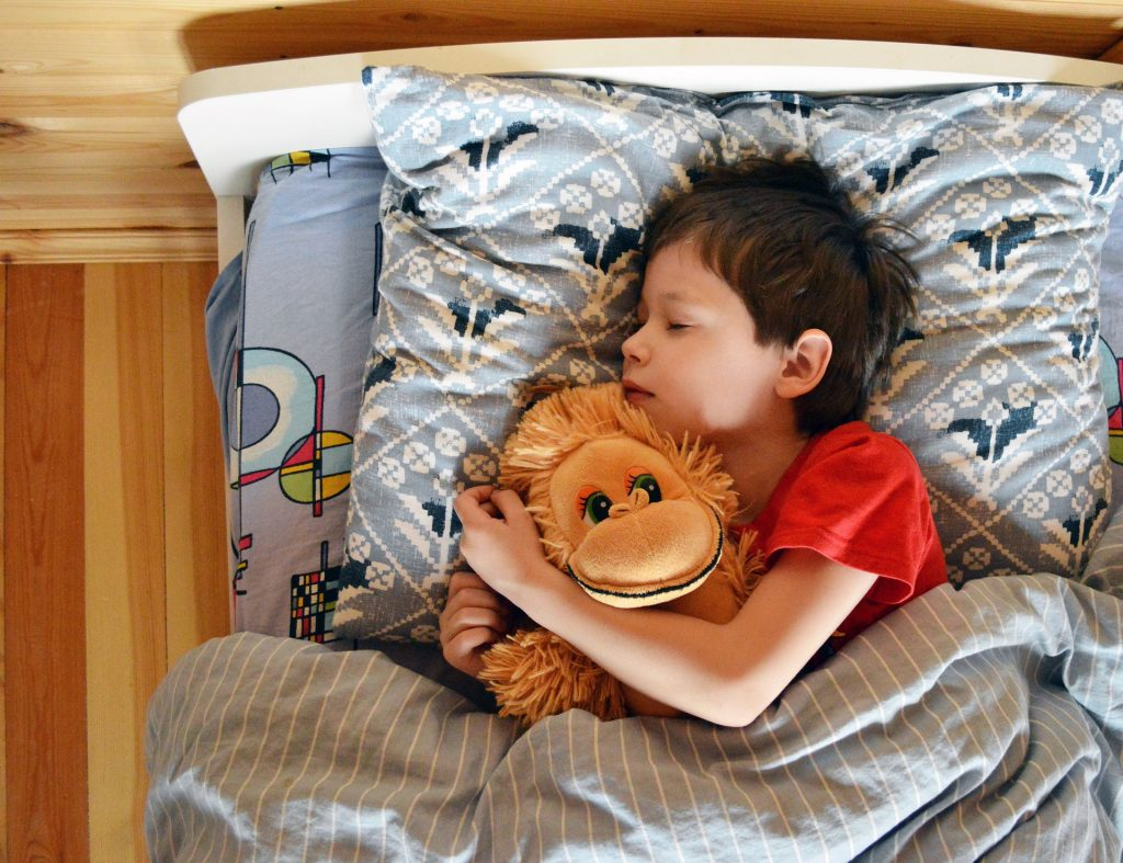 Child in bed with teddy bear
