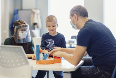 A young boy plays with toys on a table with a McMaster Children's Hospital Autism Program worker and his dad