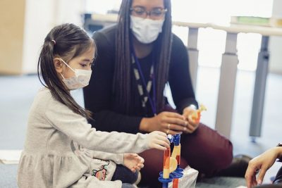 A young girl and McMaster Children's Hospital Autism Program worker sit together on the floor playing with a marble run toy