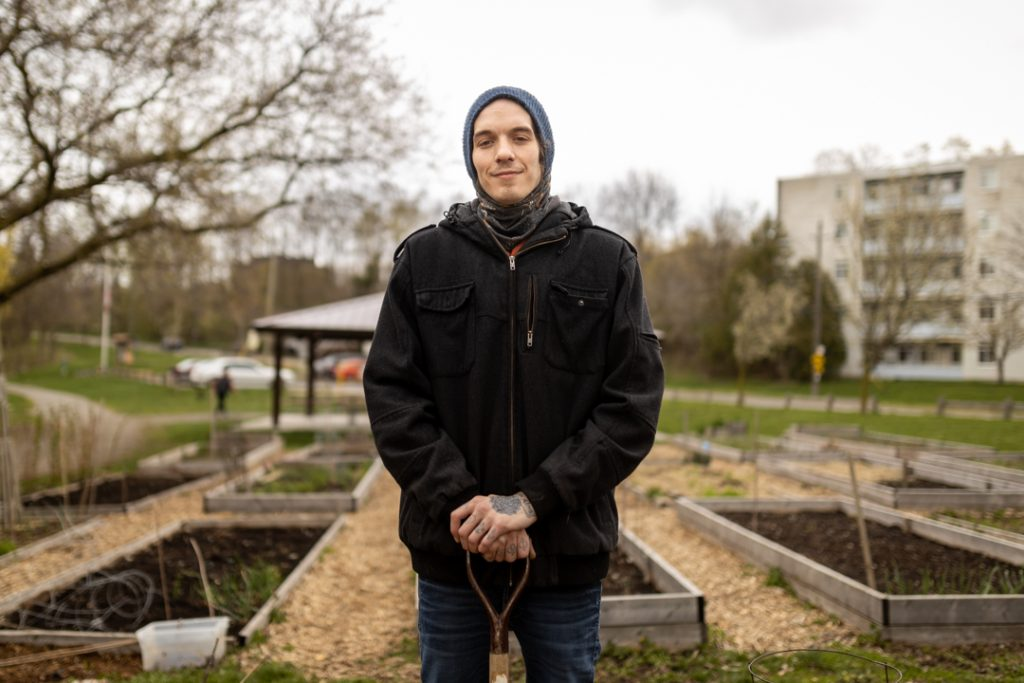 Ryan Duguay stands in the community garden wearing a hooded sweater and black jacket