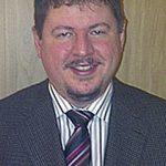 Doctor Bruce Korman, short brown hair and facial hair