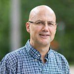 Doctor John Eikelboom, bald, glasses, short sleeve blue plaid button down shirt