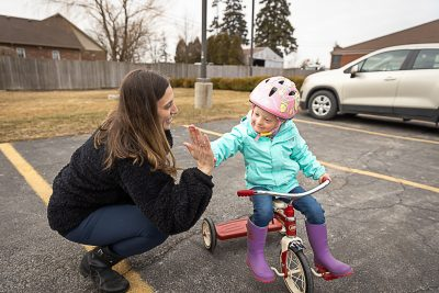A child riding a tricycle gives her mother a high five.