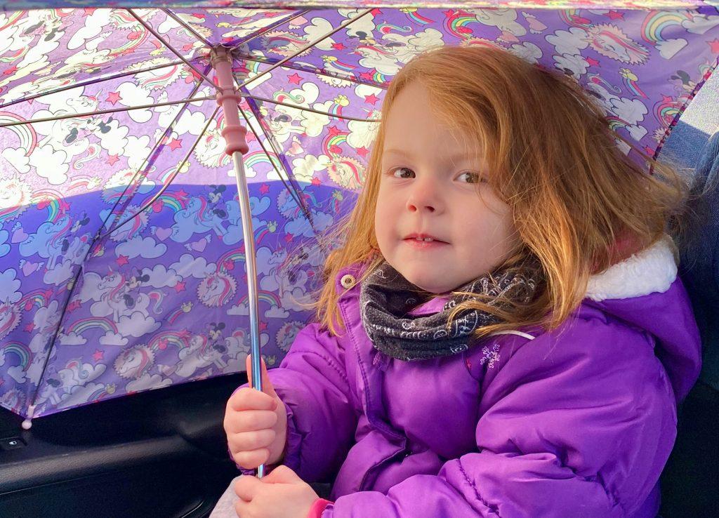 Mia is holding a purple umbrella
