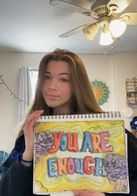 Leyda holding her art. Colourful bubble letters spelling out you are enough and hand drawn purple brains.