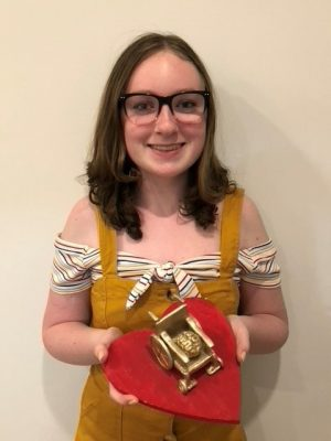 Lilly holding her sculpture art, a brain sitting in a wheelchair painted gold on a red platform.