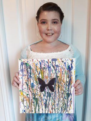 Olivia holding her art. Black butterfly on white canvas with streaks of colour in background.