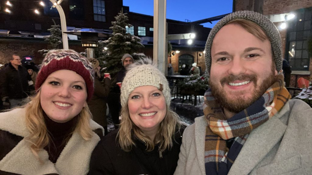 Photo of Paige, Kim, and D'Arcy Capra at an outdoor winter event. Photo taken pre-COVID.