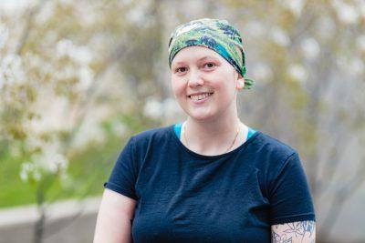 Paige Capra, patterned bandana on her head, dark blue t-shirt