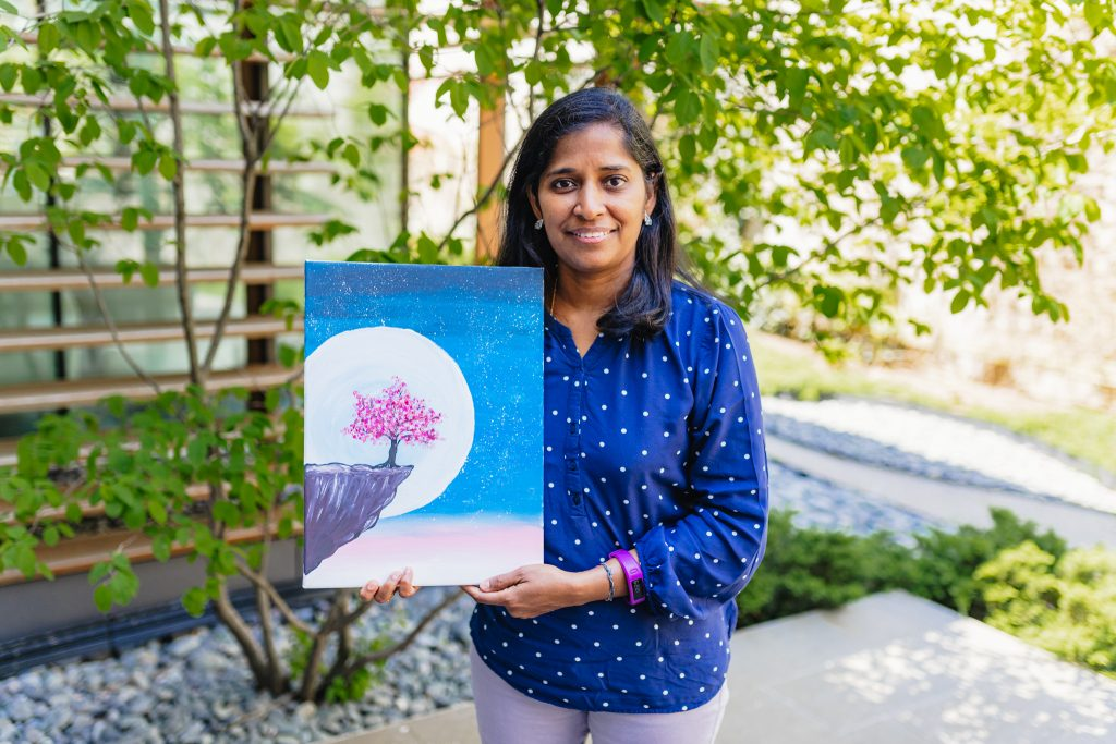 Suganya Vadivelu holding up a drawing she made during the art classes provided by Dundas Valley School of Art