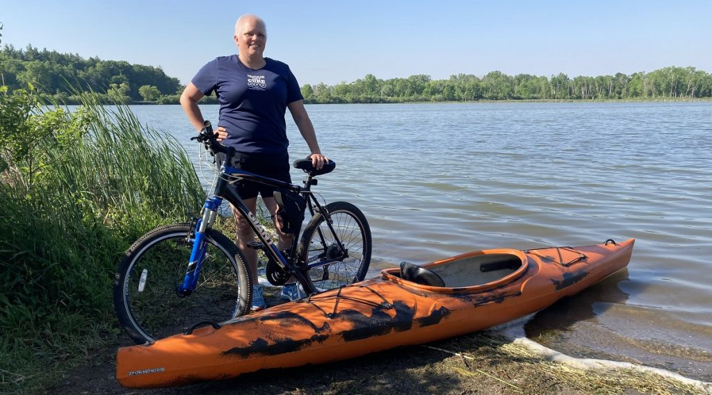Penny with her kayak and bike.