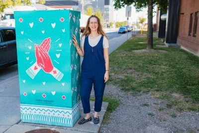 Patient advisor, Jaime Drayer standing with one of the art wrapped traffic signal boxes