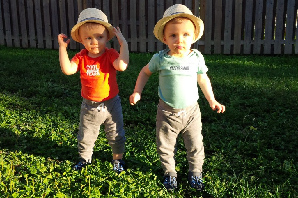 The boys as toddlers wearing hats.