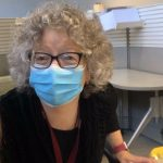 Doctor Fiona Smaill inside the vaccine clinic, wearing a blue disposable medical mask. Shoulder length grey curly hair, dark glasses.