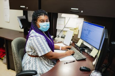 Mikeera Dobson, registered nurse at her desk in the virtual command centre