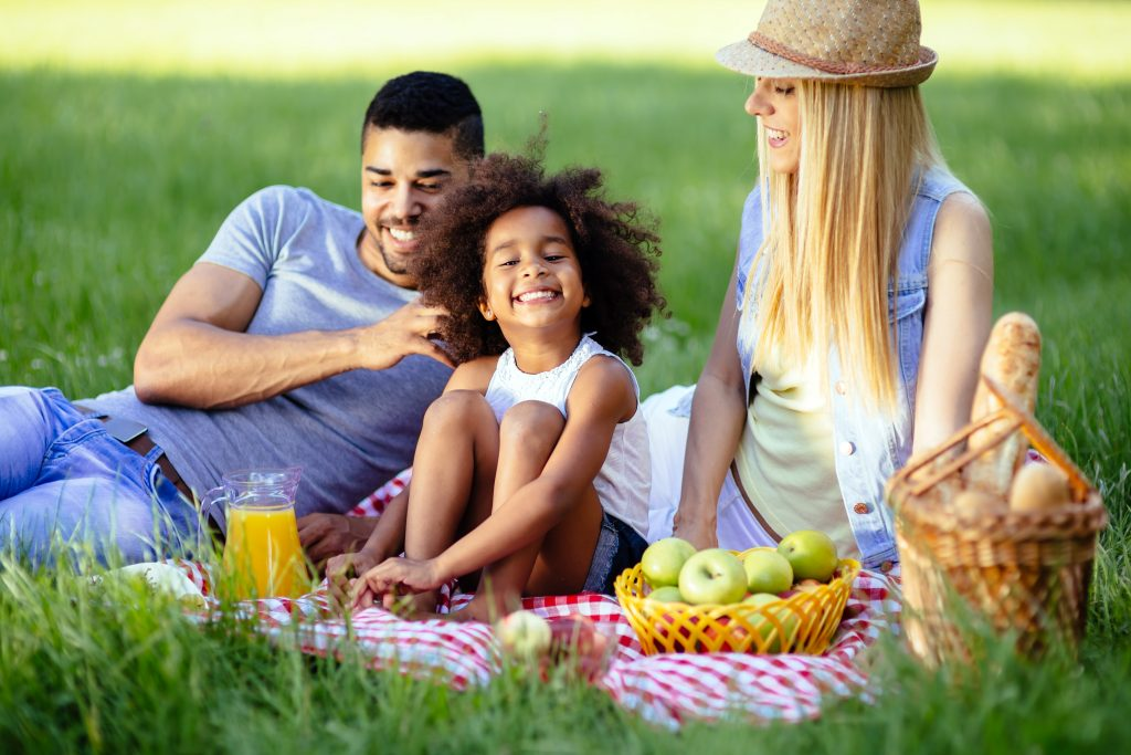 Mixed-race family, dad, mom, daughter, picnic together at a park.
