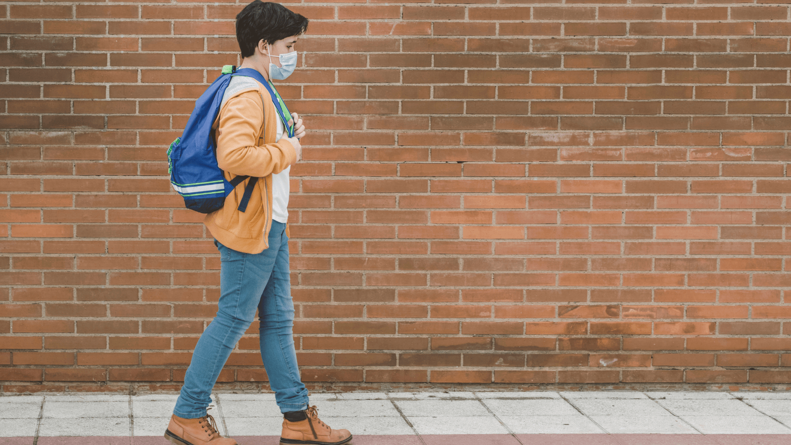 Stock photo of young student wearing face mask walking by a brick wall