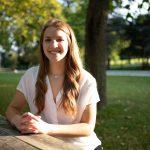 Sarah sits at a pinic table, hands folded, smiling at the camera