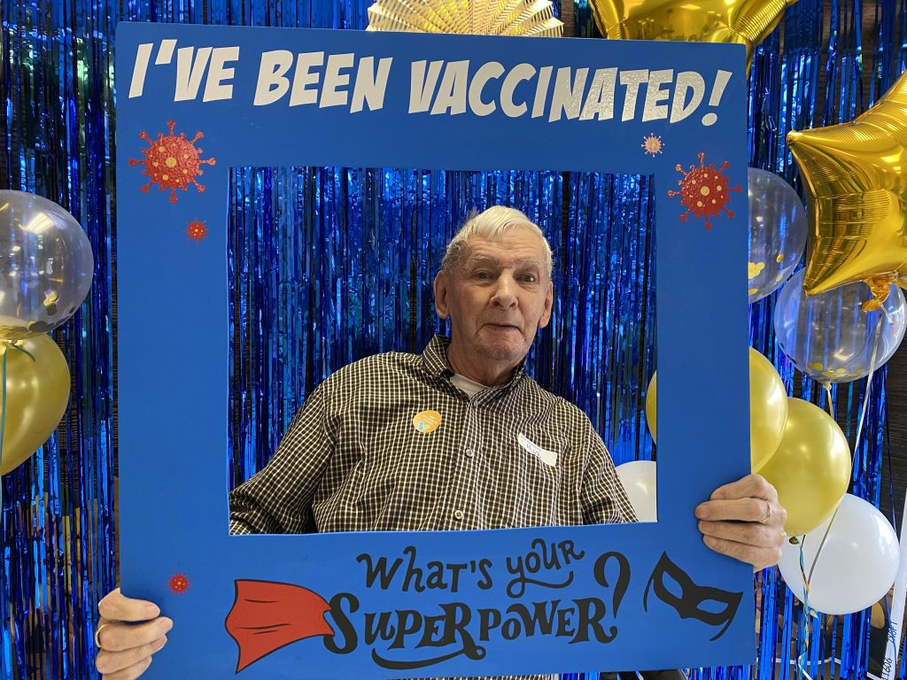 """Ed holding an """"I've been vaccinated"""" sign at Victoria Gardens long term care home"""