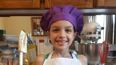 Alyssa Lodge standing in her kitchen wearing a purple chef's hat, white apron with her name displayed, holding kitchen tools in each hand