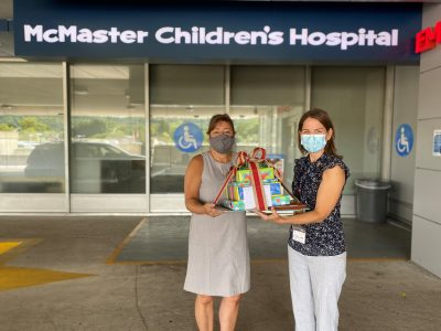 Rose giving a gift basket to Jenny from McMaster Children's Hospital Child Life department outside of the hospital.